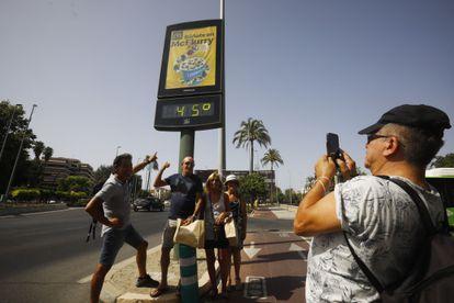 Algunos turistas fueron fotografiados en una calle de Córdoba el jueves bajo un termómetro que marca 45 grados.