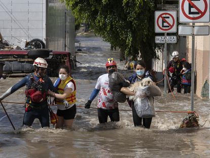 Areli Hernández y sus hijas, Loany y Danna, son rescatadas de su casa en el centro de Tula por la Cruz Roja este miércoles, tras más de 40 horas aisladas por las inundaciones