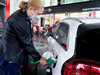 Una mujer pone gasolina a su vehículo el pasado junio, en Madrid.