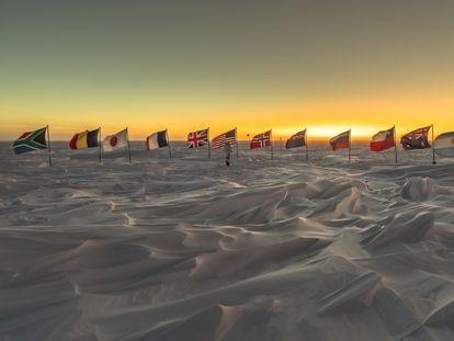 Banderas de los primeros países signatarios del Tratado Antártico tras el marcador del Polo Sur ceremonial, a unos metros del geográfico.