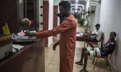 Un cliente paga en el puesto de comida rápida de Amar Diop, en Saint Louis.