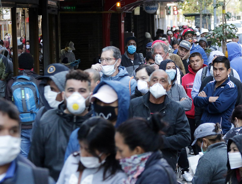 Una cola de desempleados con mascarillas esperan para solicitar el seguro de desempleo en Santiago de Chile.