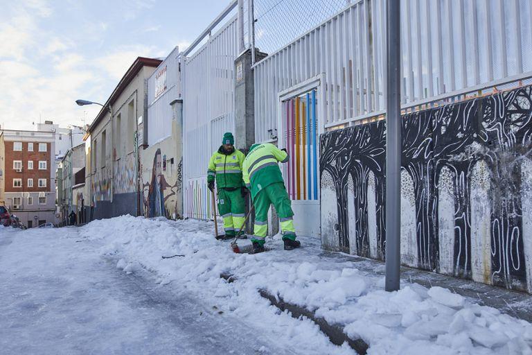 Operarios de Limpieza y Zonas Verdes del Ayuntamiento de Madrid limpian de nieve las inmediaciones del Colegio Lope de Vega de Madrid.