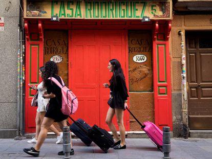 Tres jóvenes turistas llevan sus maletas por la calle de las Maldonadas de Madrid.