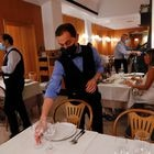A waiter sets a table at a restaurant as the Italian government is expected to announce limited restrictions for people who have not been vaccinated, including barring them from being served in indoor restaurants or from entering discos, gyms and sports stadiums, in Rome, Italy, July 22, 2021. REUTERS/Remo Casilli