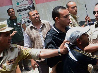 Un policía armado detiene a un hombre por tirar balas de goma en las afueras de un colegio electoral en la ciudad de Mansura.