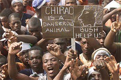 """Manifestantes contra el acuerdo de paz muestran pancartas que califican a Chirac de """"animal peligroso"""" y que piden ayuda a Bush, ayer en Abiyán."""