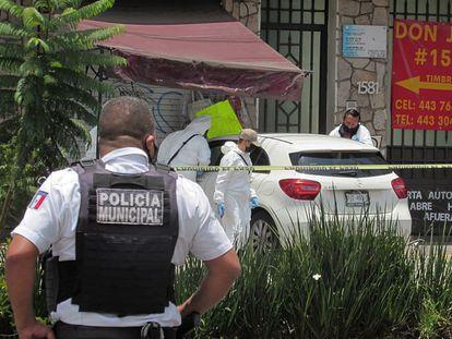La policía municipal y agentes periciales inspeccionan la escena del crimen donde fue asesinado el periodista mexicano Abraham Mendoza, en Michoacán este lunes.