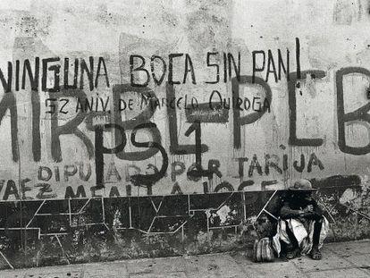 Una mujer sentada delante de una pared con pintadas, en una calle de Tarija, Bolivia.