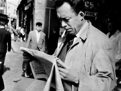 Albert Camus, fotografiado mientras fuma y lee el periódico en París, en 1953.