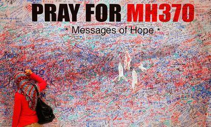 Una mujer escribe un mensaje en un mural en recuerdo de las víctimas del vuelo MH370, en el centro de Kuala Lumpur en marzo de 2014.
