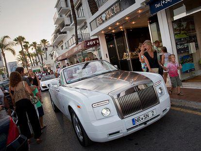 Un vehículo de alta gama circula por una calle de Puerto Banús, Málaga.