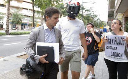 Oriol Pujol, a la izquierda, increpado ayer cundo llegaba, acompañado de un joven con casco de motorista, al domicilio de su padre.