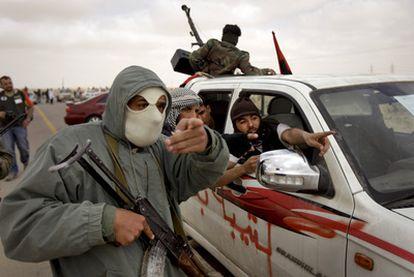 Un grupo de rebeldes libios señala una columna de humo, que no se ve en la foto, cerca de Brega.