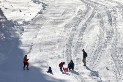 Padres y niños juegan en la nieve en la estación de esquí de La Masella.
