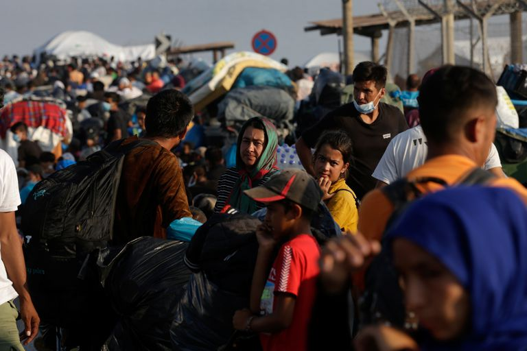 Refugiados y migrantes provenientes del campo de Moria hacen fila para entrar en un nuevo campo temporal, este viernes en la isla de Lesbos (Grecia).