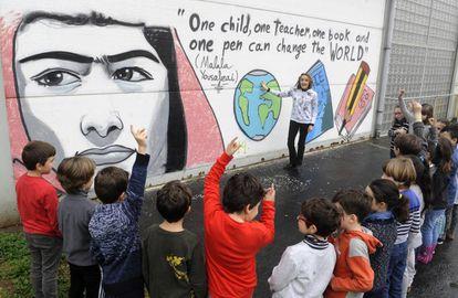 La profesora Leticia Secall da sus explicaciones ante una pintada en homenaje a Malala, Nobel de la Paz en 2014.