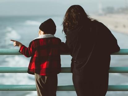 Una madre y su hijo frente al mar.