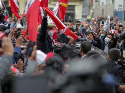 The presidential candidate for the Peru Libre party, leftist Pedro Castillo, flutters a national flag as he arrives at the party's headquarters in Lima on June 7, 2021, a day after runoff elections. - Right-wing populist Keiko Fujimori held a narrow lead Monday in Peru's presidential election, but the crisis-hit nation's race was too close to call as votes were still being tabulated from countryside bastions of support for radical leftist Pedro Castillo. With over 95% of the votes tallied, the result of the runoff election is still unknown. (Photo by Luka GONZALES / AFP)