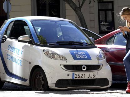 Una usuaria consultando su móvil junto a un coche de Car2Go.