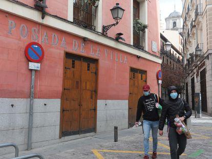 Dos ciudadanos pasan ante un restaurante de la Cava Baja que ha cerrado sus puertas. KIKE PARA