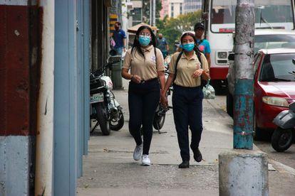 Dos estudiantes caminan por las calles de Caracas.