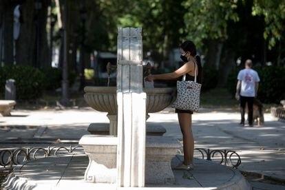Una mujer junto a una de las fuentes del Paseo del Prado, este jueves.