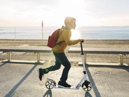 Un niño juega con un patinete eléctrico en la orilla de la playa.