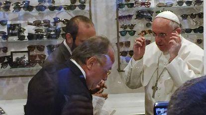 El Papa se prueba unas gafas en la tienda de Alessandro Spiezia (en primer término).
