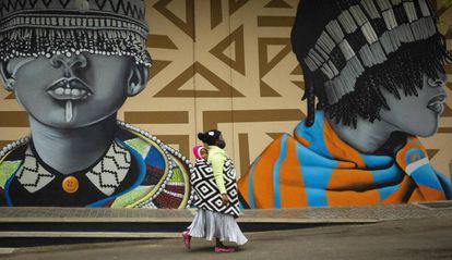 Una madre pasea con su hijo junto a unos grafitis en las calles de Johanesburgo (Sudáfrica).