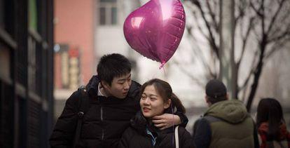 Una pareja camina por Pekín el día de San Valentín.