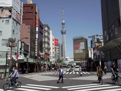 Viandantes y vehículos en un cruce de calles en Tokio.