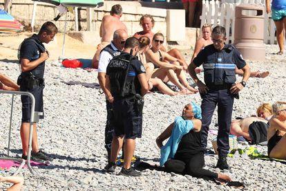 Una mujer se quita la camisa mientras la policía le pone una multa en Niza.