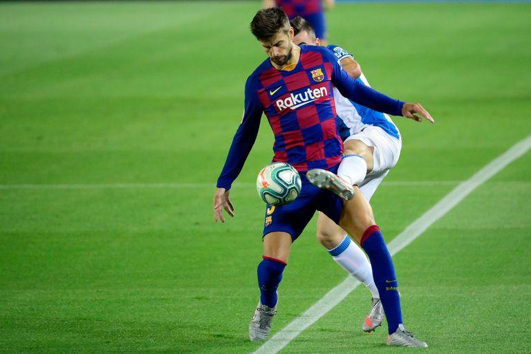 Piqué y Campuzano disputan el balón en el derbi.