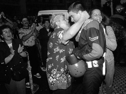 Una mujer abraza a un policía autonómico vasco (ertzaina) mientras custodiaba la sede de HB en Ermua.