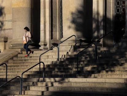 Una mujer baja la escalinata de la entrada de la sede central de Correos en Barcelona.