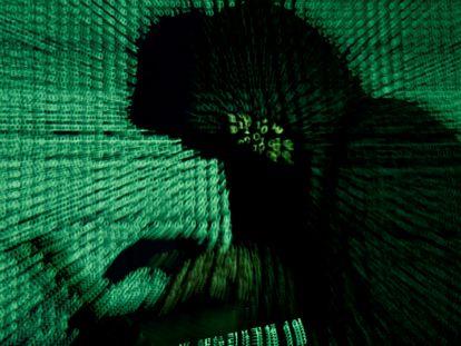 Un hombre sostiene una ordenador mientras se proyecta un código cibernético sobre él.