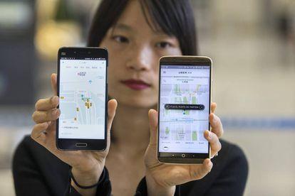 Una mujer china muestra las aplicaciones de Didi y de Uber en China