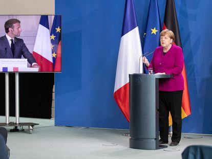 El presidente Emmanuel Macron, en pantalla, y la canciller Angela Merkel, durante una rueda de prensa, este lunes, en Berlín.