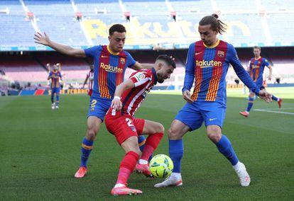 El centrocampista del Atlético Yannick Carrasco es presionado por Sergino Dest (a la izquierda) y Antoine Griezmann durante el Barcelona-Atlético del pasado sábado. / Albert Gea (REUTERS)