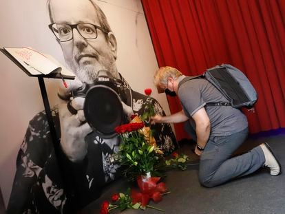 El director de la revista 'Enderrocs' coloca unas flores delante de la fotografía del fotógrafo fallecido este lunes Xavier Mercadé, en la exposición que le decida el Palau Robert, que se prorroga.