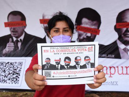 Una mujer muestra un cartel a favor de la consulta popular de este domingo en México.