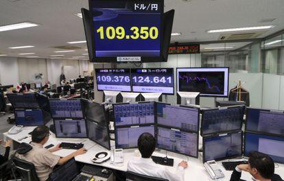 Varios operadores japoneses trabajan delante de pantallas que marcan el tipo de cambio entre el yen y el dólar estadounidense.