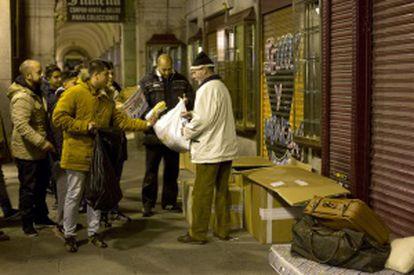 Integrantes de la Iglesia Evangélica Filadelfia de Orcasitas entregan alimentos en la plaza Mayor.