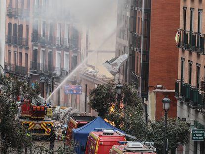 Los bomberos echan agua en el edificio situado en la calle Toledo 98, tras al explosión.