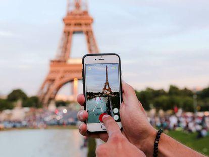 Un hombre se dispone a capturar un 'pokémon' frente a la Torre Eiffel, en París.