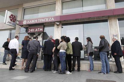 La gente hace cola ante un cajero del Laiki Bank, en Nicosia.
