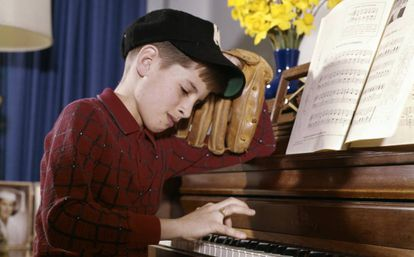 Niño en clase de piano, pero deseando jugar al béisbol