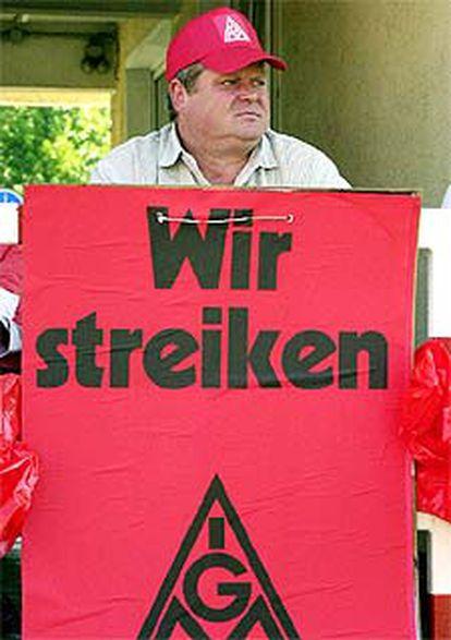 """Un metalúrgico con una pancarta que dice: """"Estamos en huelga""""."""