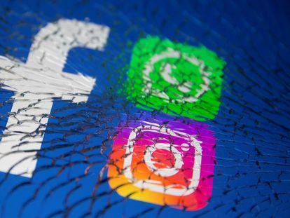 Los logos de Facebook, Whatsapp y Instagram en una pantalla rota.